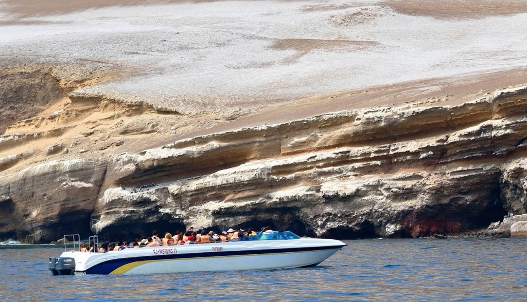Paracas, Pisco. March 24, 2019 - group of tourists sailing by boat through the bay of Paracas towards the Ballesta Islands in Pisco, Peru