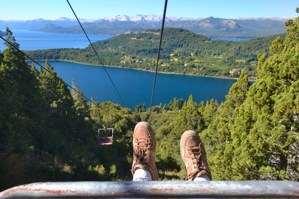 Feet of a tourist on the background of mountains and lake landscape view from cable car of Cerro Campanario in Bariloche Argentina.