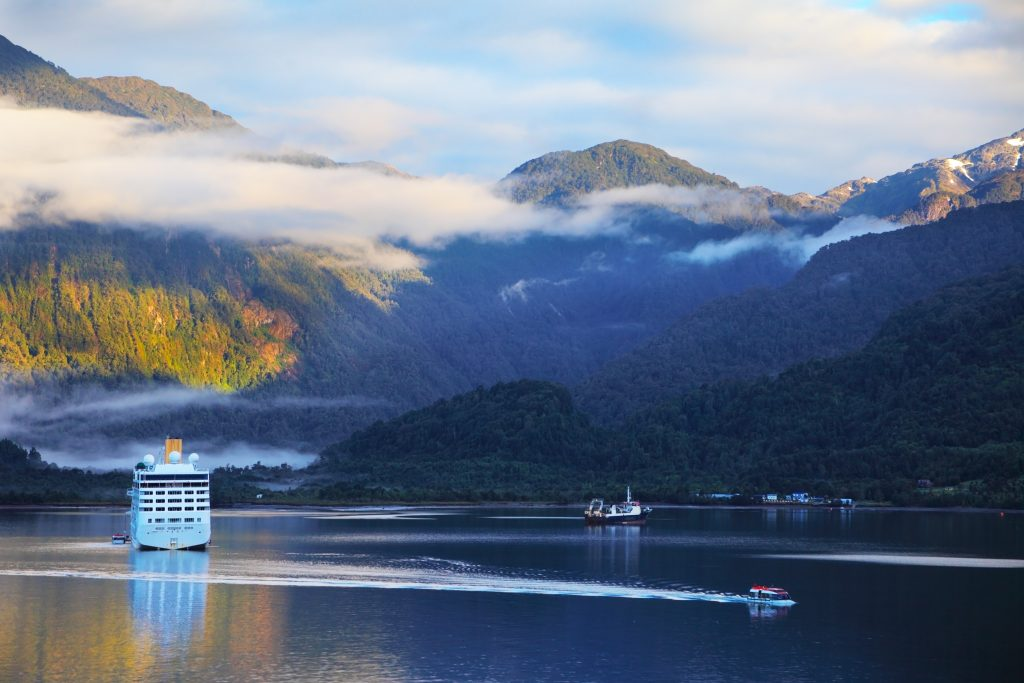 Snow-white tourist boat lit rising sun. On the mountains are thin clouds. Sunrise in the Chilean fjord