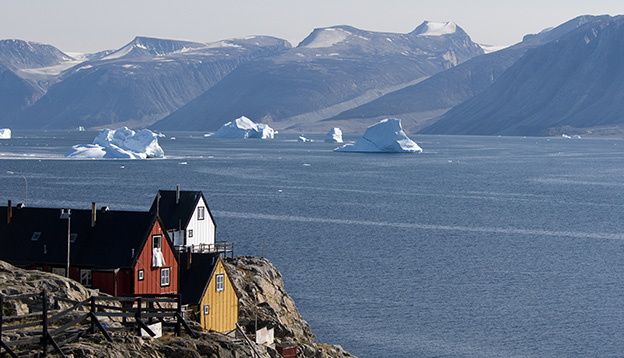 Houses overlook an iceberg-laden fjord of Baffin Bay in the small village of Uummannaq, Greenland