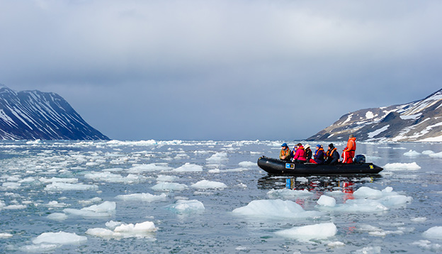 Tourists from the National Geographic Explorer cruise ship explore a fjord in the Arctic via a zodiac
