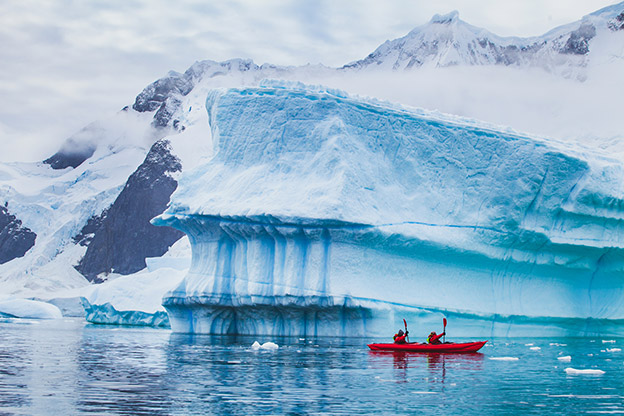 People paddling on kayak near iceberg, Antarctica.