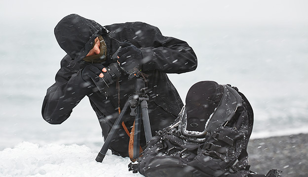 Photographer changing lens in challenging conditions in a snow storm