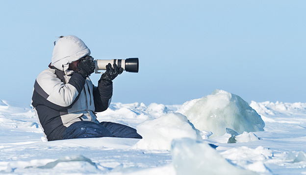 Phtographer photographing with telephoto lens in the Arctic ice