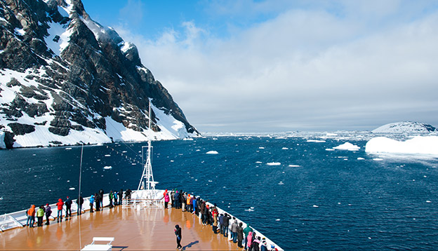 Peopl stand on the deck as small ship crusies Antarctic waters.