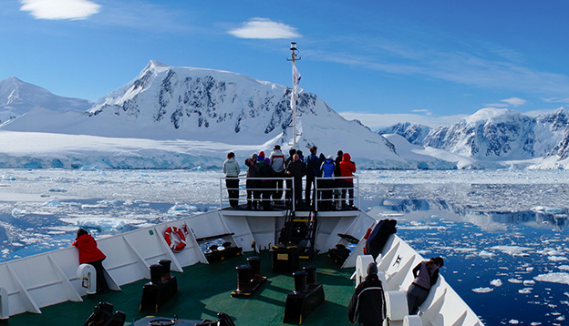 Passengers stand on the deck of a ship and look out to Antarctica.