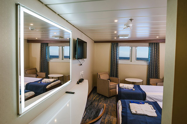View of 2 beds and a mirror in a ship cabin
