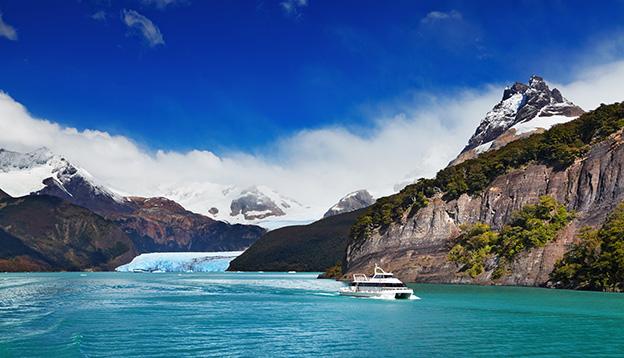 A small ship crusing past Spegazzini Glacier, Argentino Lake, Patagonia, Argentina