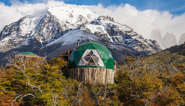 A dome tent at EcoCamp Patagonia in front of a snow capped mountain