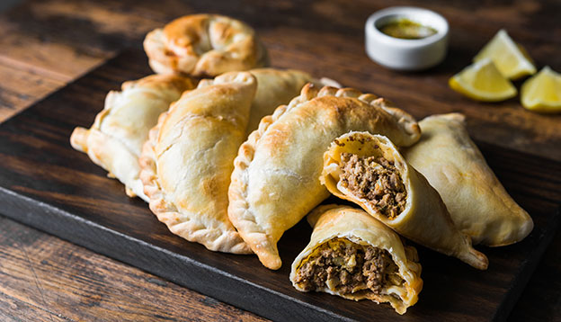 South American culture: Traditional baked Argentine empanadas savoury pastries with meat beef stuffing against wooden background