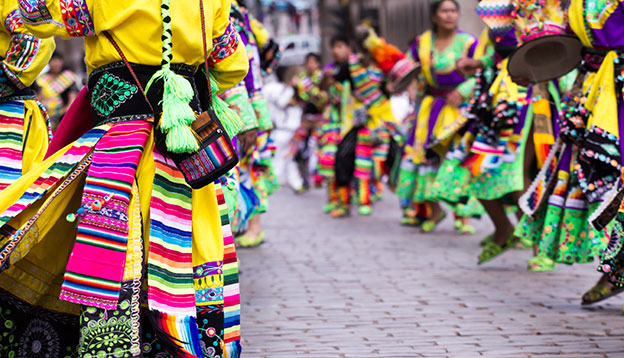 South American culture: Peruvian dancers in brightly coloured clothes at the parade in Cusco