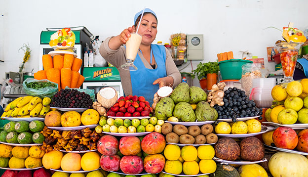 South American culture: Bolivian woman gives the cup with freshly squizzed juice on the market in the city of Sucre with abundance of fruits on the foreground