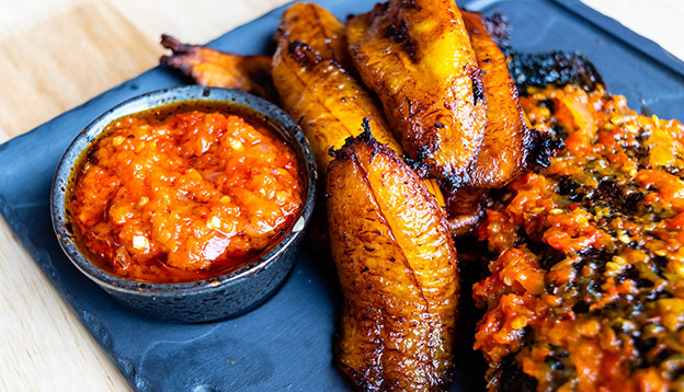 Fried slices of ripe plantain and chilli sauce on a blue plate