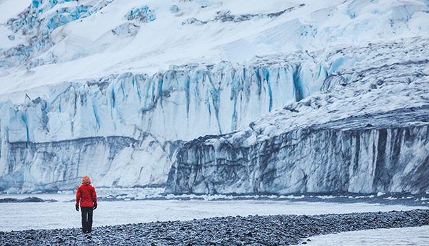 A solo traveller in a red jacket walks in front of a large ice cliff in Antarctica