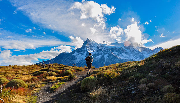 Person hiking in Torres del Paine National Park with mountains in the background