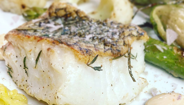 Close up of plate with Patagonian toothfish on a plate with vegetables