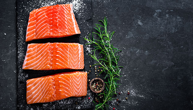 3 fillets of fresh salmon on a black chopping board with salt