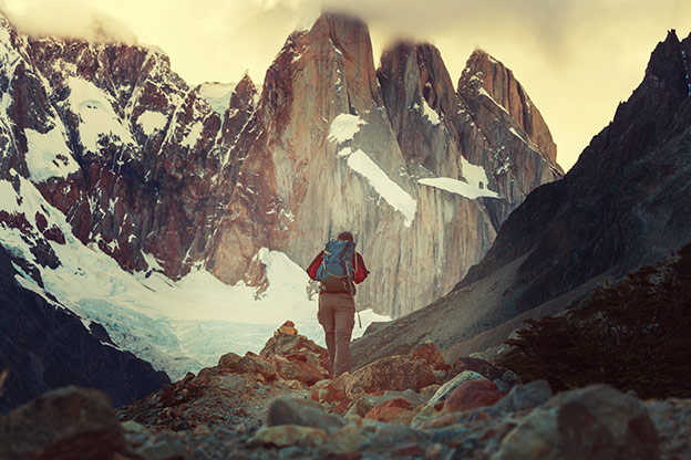 A person hiking in Patagonia with large mountains in the background