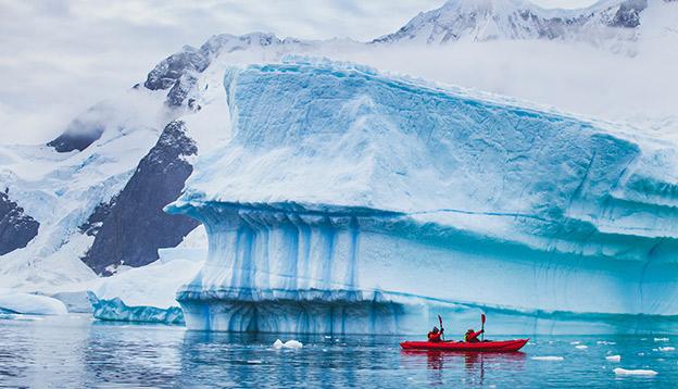 2 people kayak alongside icebergs in Antarctica