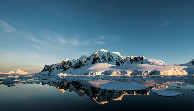 Mountains and glaciers with their reflection in the water.