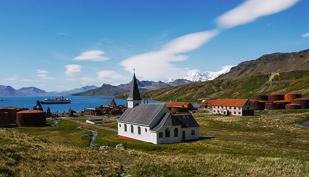 Remains of early 19th century Norwegian whaling settlement with rusting tanks, abandoned buildings and restored Lutheran church. Grytviken, South Georgia