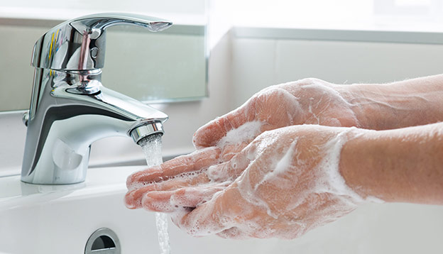 Person washing hands with soap under the faucet with water