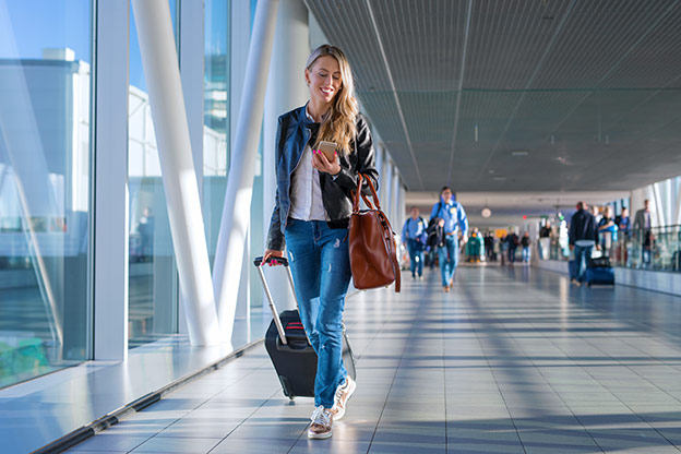 Woman walking in airport checking her phone