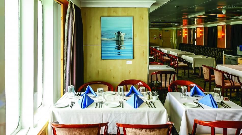 Dining tables are set with white tablecloths and cutlery on the Ocean Endeavour